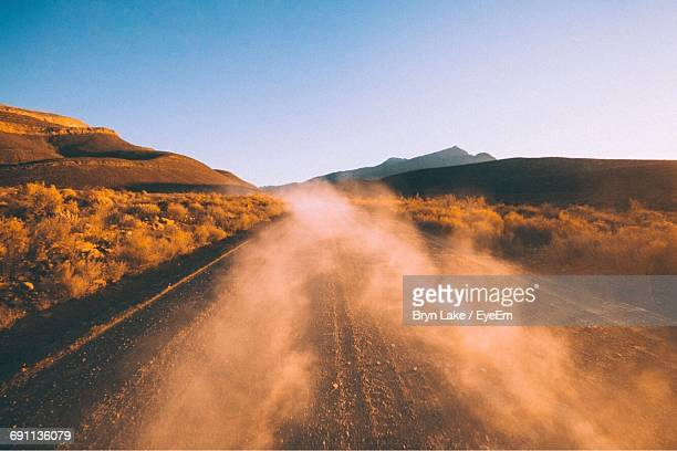scenic view of road in mountains against clear sky - dust stock pictures, royalty-free photos & images