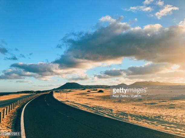 Scenic View Of Road Through Desert During Sunset