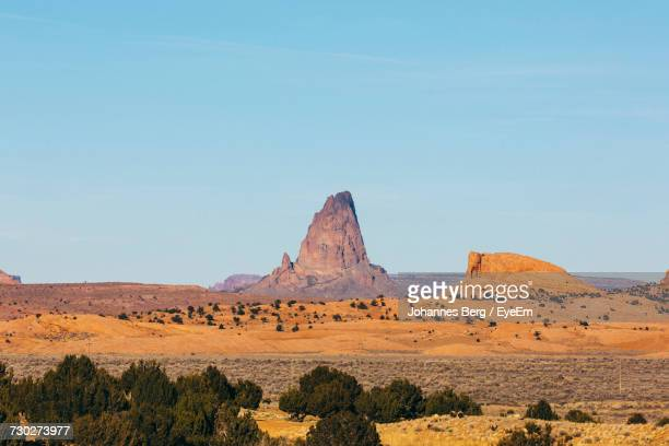 scenic view of rock formation against clear sky - shiprock stock photos and pictures