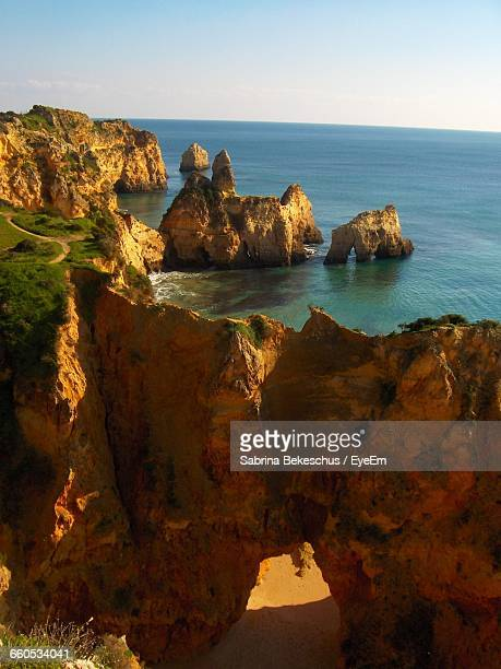 scenic view of rock formation and cliffs next to sea - alvor stock pictures, royalty-free photos & images