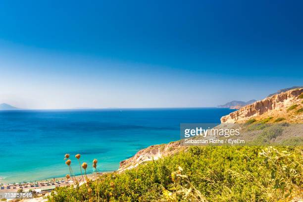 Scenic View Of Rock Formation By Sea Against Clear Blue Sky