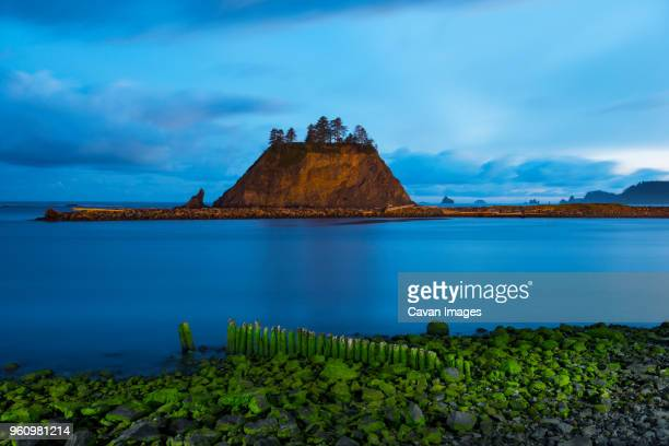 Scenic view of rock formation in sea against cloudy sky at dusk