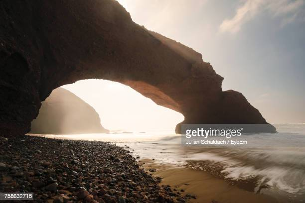 scenic view of rock formation in sea against sky - arch stock pictures, royalty-free photos & images
