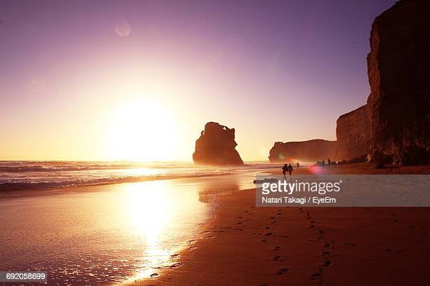 Scenic View Of Rock Formations And Sea Against Clear Sky During Sunset
