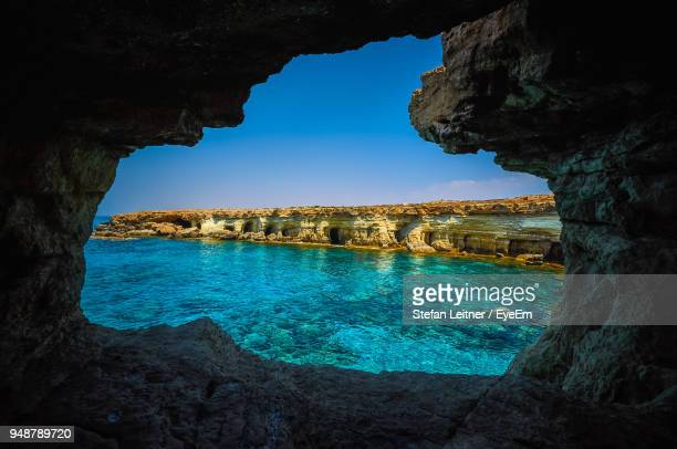 scenic view of rock formations in sea seen through cave - republic of cyprus stock pictures, royalty-free photos & images