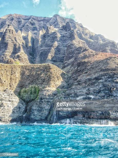 scenic view of rock in sea against sky with waterfall flowing into ocean - krings stock pictures, royalty-free photos & images