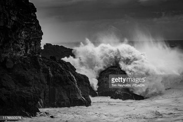 scenic view of rocks and sea against sky - big wave surfing stock pictures, royalty-free photos & images