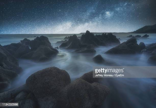 scenic view of rocks at sea against sky at night - flowing cape stock pictures, royalty-free photos & images