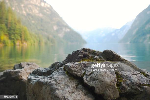 scenic view of rocks in lake against mountains - fels stock-fotos und bilder