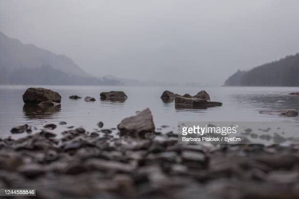 scenic view of rocks in lake against sky - rock stock pictures, royalty-free photos & images