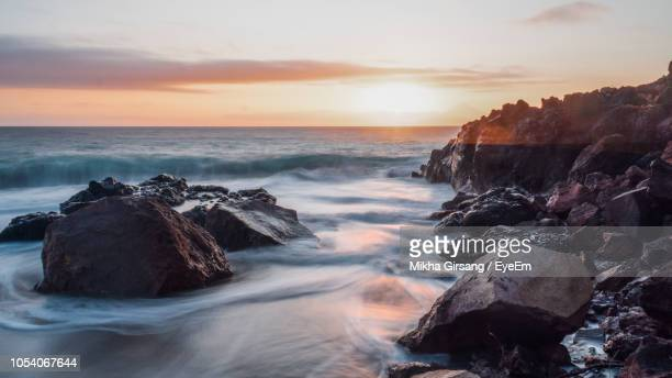 scenic view of rocks in sea against sky during sunset - rocky coastline stock pictures, royalty-free photos & images