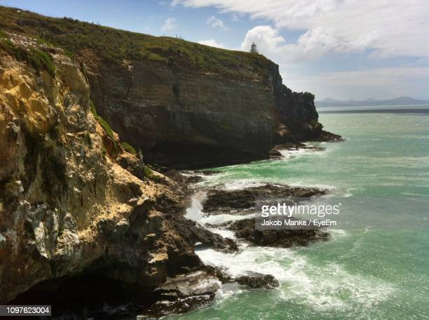 scenic view of rocks in sea against sky - dunedin new zealand stock pictures, royalty-free photos & images