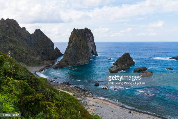 scenic view of rocks in sea against sky - rocky coastline stock pictures, royalty-free photos & images