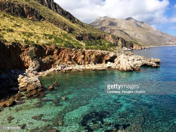 scenic view of rocks in sea against sky - loredana perugini stock pictures, royalty-free photos & images