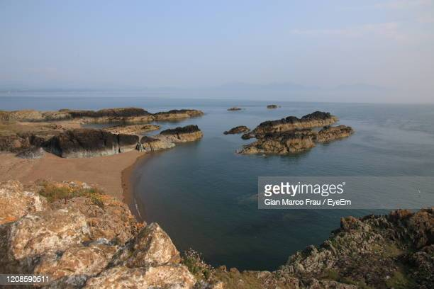 scenic view of rocks in sea against sky - frau photos et images de collection