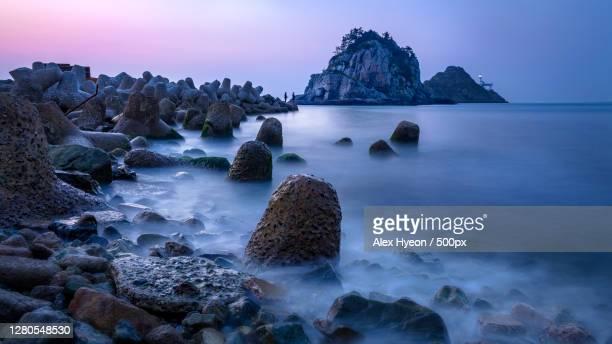 scenic view of rocks in sea against sky,busan,south korea - zuid korea stockfoto's en -beelden