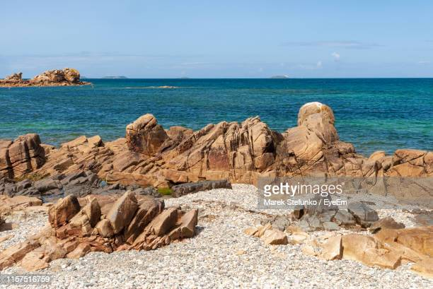 scenic view of rocks on beach against sky - marek stefunko stock photos and pictures