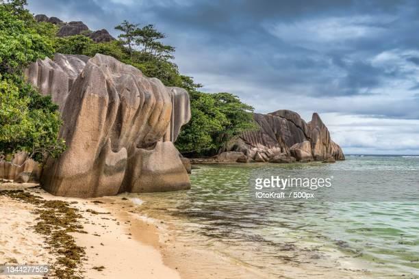 scenic view of rocks on beach against sky,victoria,seychelles - wasser imagens e fotografias de stock