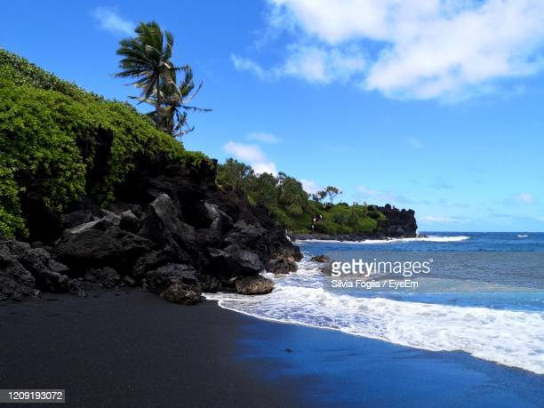 scenic view of rocks on black volcanic beach against sky - punalu'u_beach stock pictures, royalty-free photos & images