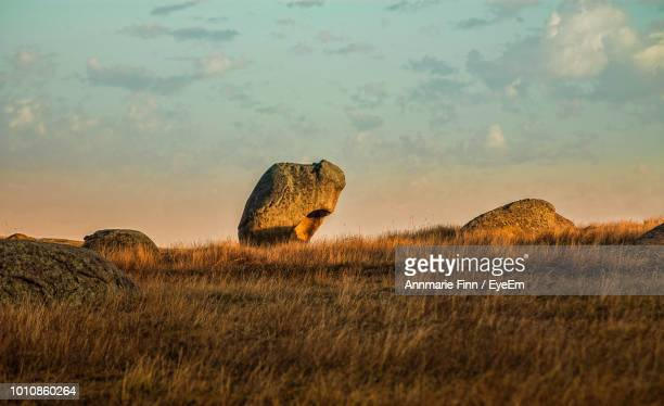 Scenic View Of Rocks On Field Against Sky During Sunset
