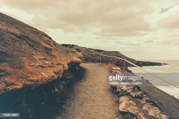 scenic view of rocky beach against cloudy sky - bortes stockfoto's en -beelden