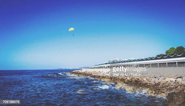 Scenic View Of Rocky Coastline Against Clear Blue Sky With Parasailer