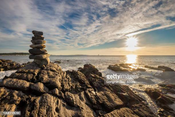 Scenic view of rocky coastline at sunrise with cairn stones