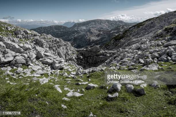 scenic view of rocky mountains against sky - christian soldatke stock-fotos und bilder