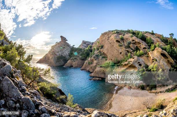 scenic view of rocky mountains and sea against sky - ラシオタ ストックフォトと画像