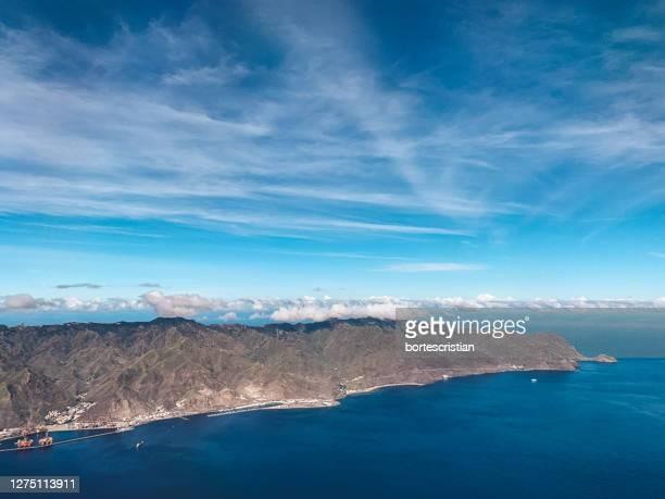 scenic view of rocky sea coast against sky - bortes stock-fotos und bilder