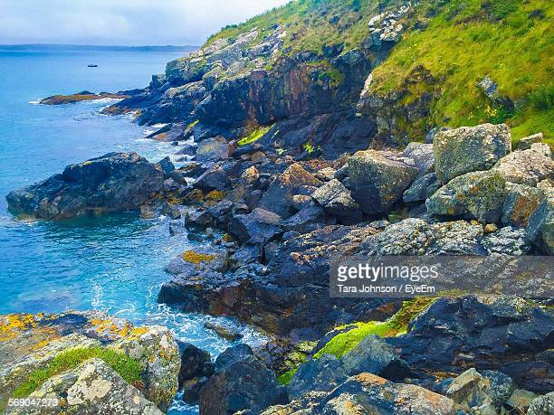 scenic view of rocky sea shore against sky - st ives stock pictures, royalty-free photos & images