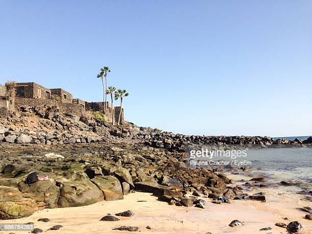 Scenic View Of Rocky Shore Against Clear Sky