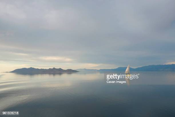 scenic view of sailboat in lake against cloudy sky - great salt lake stock pictures, royalty-free photos & images