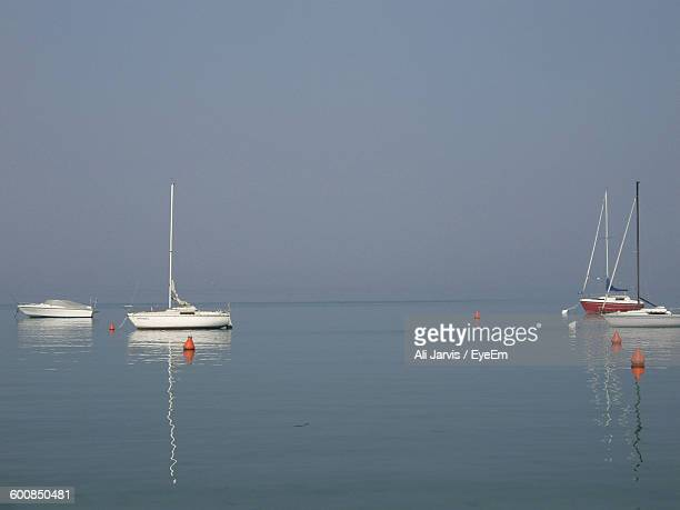 Scenic View Of Sailboats Anchored In Ocean Against Clear Sky
