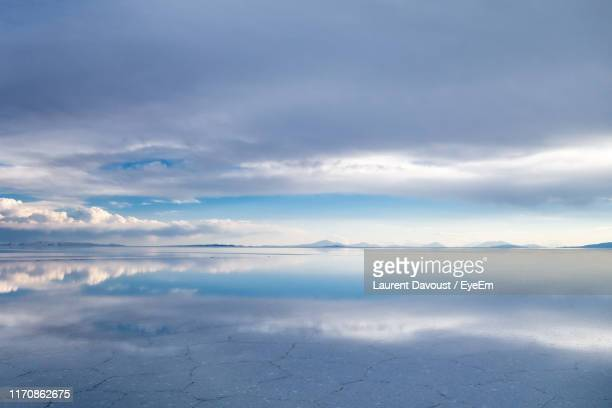 scenic view of salt flat against cloudy sky - ウユニ ストックフォトと画像