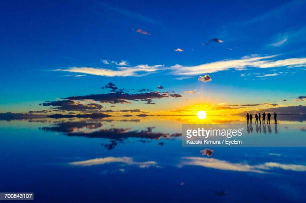 scenic view of salt flat against sky at sunset - ウユニ ストックフォトと画像