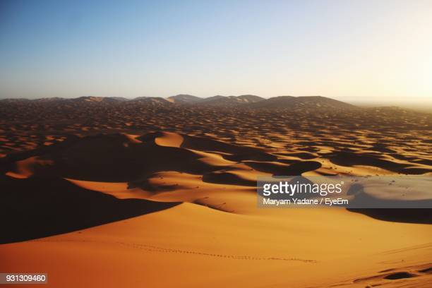 scenic view of sand dunes against clear sky at sunset - merzouga stock pictures, royalty-free photos & images