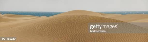 scenic view of sand dunes against clear sky - bortes stockfoto's en -beelden