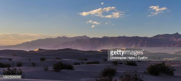 Scenic View Of Sand Dunes Against Sky During Sunset