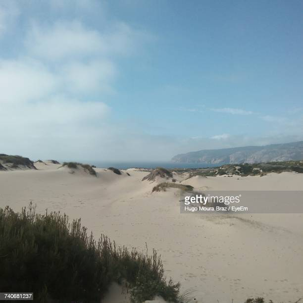 scenic view of sand dunes against sky - moura stock photos and pictures