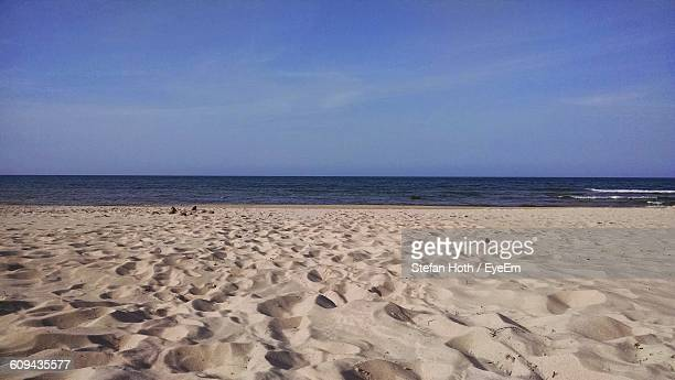 Scenic View Of Sandy Beach Against Blue Sky