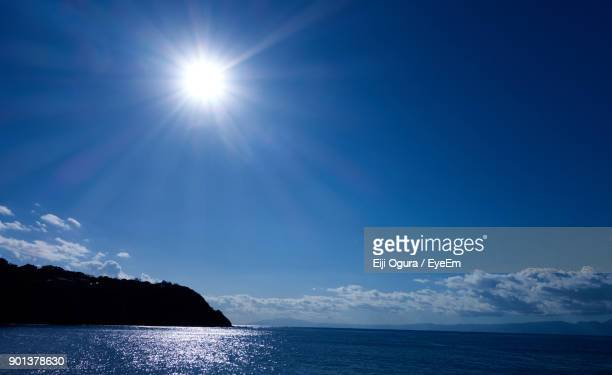 scenic view of sea against blue sky - 太陽の光 ストックフォトと画像