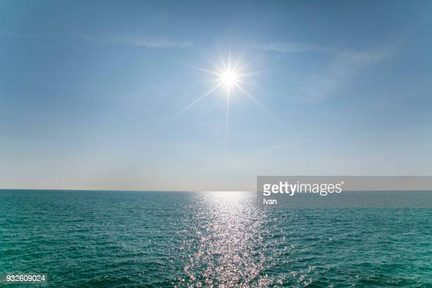 scenic view of sea against clear blue sky and sunlight - blendenfleck stock-fotos und bilder