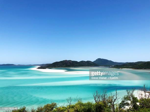 scenic view of sea against clear blue sky - whitehaven beach stock-fotos und bilder
