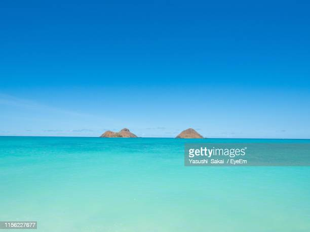 scenic view of sea against clear blue sky - kailua stock pictures, royalty-free photos & images