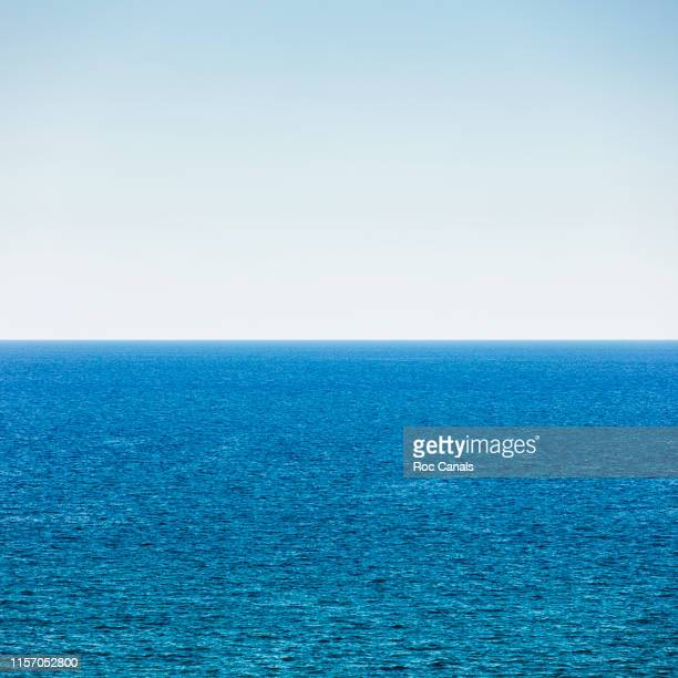 scenic view of sea against clear blue sky - atlantik stock-fotos und bilder