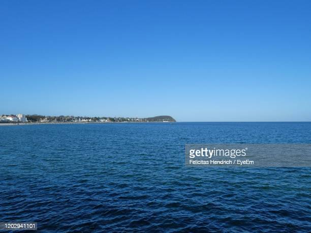 scenic view of sea against clear blue sky - uferviertel stock-fotos und bilder