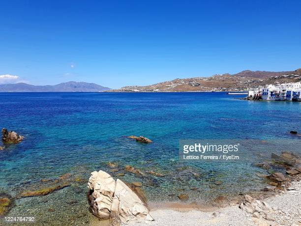 scenic view of sea against clear blue sky - ver a hora stockfoto's en -beelden
