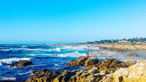 scenic view of sea against clear blue sky - pebble beach california stockfoto's en -beelden