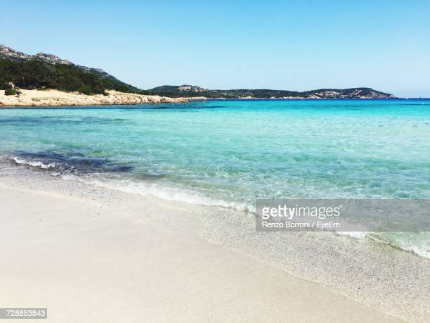 scenic view of sea against clear blue sky - costa smeralda stock pictures, royalty-free photos & images